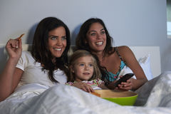 Young girl watching TV in bed with gay female parents Stock Photos