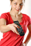 Young girl watching tv using a remote control Royalty Free Stock Photo