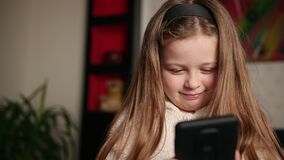 A young girl watching video on smartphone while lying sofa. Lass peeking