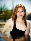 Young girl in the water in summer river. Against blur background Stock Photography
