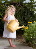 Young girl watering flowers Royalty Free Stock Images