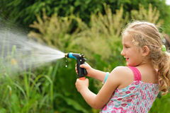 Young girl watering plants. Royalty Free Stock Photos