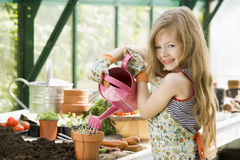 Young girl watering plants in greenhouse stock image
