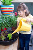 Young girl watering salad smiling Stock Photography