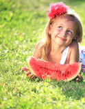 Young girl with watermelon. Smiling blond girl on the grass holding a slice of watermelon stock photo