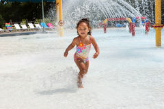Young girl at a waterpark. Young girl dances in the water at a waterpark. Water is spraying from a play system Stock Photos
