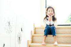 Young girl wating on the step. Warm color tone.Portrait young Thai girl sit on the step at home beside the glass window royalty free stock images
