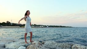 Young girl waving her hands like a winged bird on the stony beach. Young girl in white dress waving her hands like a winged bird on the stony beach. Woman like stock video footage