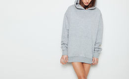 Young girl wearing blank and oversize long hoody. White background Royalty Free Stock Photo