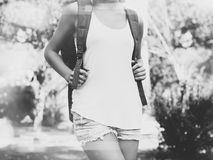 Young girl wearing blank t-shirt and backpack. Outdoor background. Horizontal mockup, blurred, bokeh effect. Black white Royalty Free Stock Photo