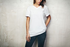 Young girl wearing blank t-shirt and black jeans. Concrete wall background Royalty Free Stock Photography
