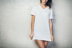 Young girl wearing blank t-shirt. Concrete wall background. Horizontal Stock Photos