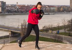 Young girl wearing boxing gloves throwing a punch - martial arts Royalty Free Stock Photo