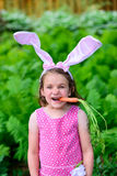 Young Girl Wearing Bunny Ears with Carrot in Her Mouth royalty free stock photography