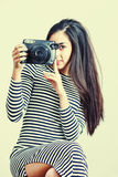 Young girl wearing casual cloth posing with instant camera. Royalty Free Stock Photo