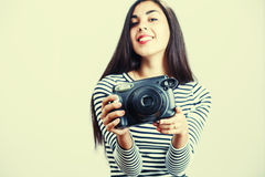 Young girl wearing casual cloth posing with instant camera. Stock Photo