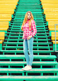 Young girl wearing a checkered pink shirt and jeans Royalty Free Stock Photos