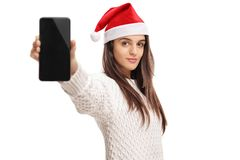Young girl wearing a christmas hat and showing a phone. Isolated on white background Stock Image
