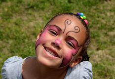 Young Girl Wearing Face Paint and Smiling Brightly. Young Girl Wearing Pink and Black Face Paint and Smiling Very Brightly stock photo