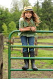 Young Girl Wearing a Fedora. A young smiling country girl with long hair wearing a straw hat and farm boots standing on a cattle gate Stock Image