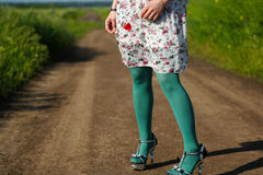 Young girl wearing floral dress. Poppy in her hand, alley in the field Stock Photo
