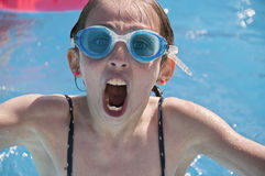 Young girl wearing goggles in apool. stock photography