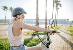 Young girl wearing helmet and protective glasses sits near electric bicycle stock images