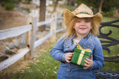 Young Girl Wearing Holiday Clothing Holding a Gift Royalty Free Stock Photography