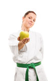 Young girl wearing kimono and offering an apple Royalty Free Stock Photos