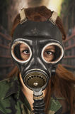 Young girl wearing military uniform and gas mask Royalty Free Stock Photo