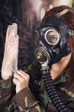 Young girl wearing military uniform and gas mask Stock Photos