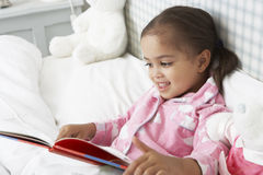 Young Girl Wearing Pajamas In Bed Reading Book Royalty Free Stock Image