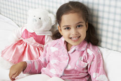 Young Girl Wearing Pajamas In Bed Reading Book Royalty Free Stock Photography