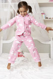 Young Girl Wearing Pajamas Jumping On Bed Royalty Free Stock Photos