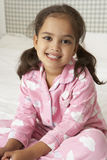 Young Girl Wearing Pajamas Sitting On Bed Royalty Free Stock Photos