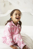 Young Girl Wearing Pajamas Sitting On Bed Royalty Free Stock Image