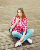 Young girl wearing a pink shirt with backpack sitting Royalty Free Stock Photos