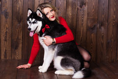 Young girl wearing red dress with her husky dog Stock Images
