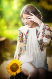 Young girl wearing Romanian traditional blouse holding a sunflower outdoor shot. Portrait of beautiful blonde girl Stock Photos