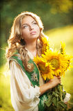 Young girl wearing Romanian traditional blouse holding sunflowers outdoor shot. Portrait of beautiful blonde girl with sunflowers Stock Photos