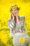 Young girl wearing Romanian traditional blouse posing in canola field, outdoor shot. Portrait of beautiful blonde with wreath Stock Photos
