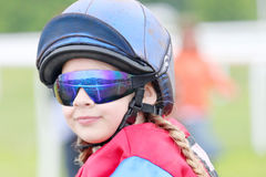 Young girl wearing sun glasses sitting on a pony Royalty Free Stock Image