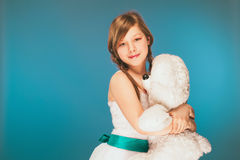 Young girl wearing a white dress with a cute smile on Holiday. White toy Bear Stock Images