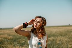 Young girl wearing a white dress in hippie style posing in a wheat field stock photo