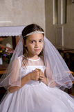 Young girl wearing white dress holding rosary Royalty Free Stock Image