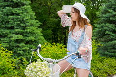 Young girl wearing a white hat sitting on her bicycle Stock Photos
