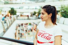 Young Girl Wearing White Shirt With Drink Coca-Cola Slogan Sign In Modern Shopping Mall Stock Photography