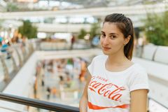 Young Girl Wearing White Shirt With Drink Coca-Cola Slogan Sign In Modern Shopping Mall Stock Photo