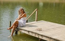 Young girl wearing a white sitting by the river in summer afternoon. Casual young girl wearing a white sitting by the river in summer afternoon Stock Photos