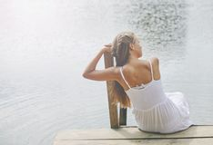 Young girl wearing a white sitting by the river in summer afternoon. Casual young girl wearing a white sitting by the river in summer afternoon Royalty Free Stock Photos